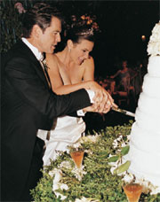 As The Bride And Groom Cut Their Six Tiered Wedding Cake They Were Showered With Rose Petals